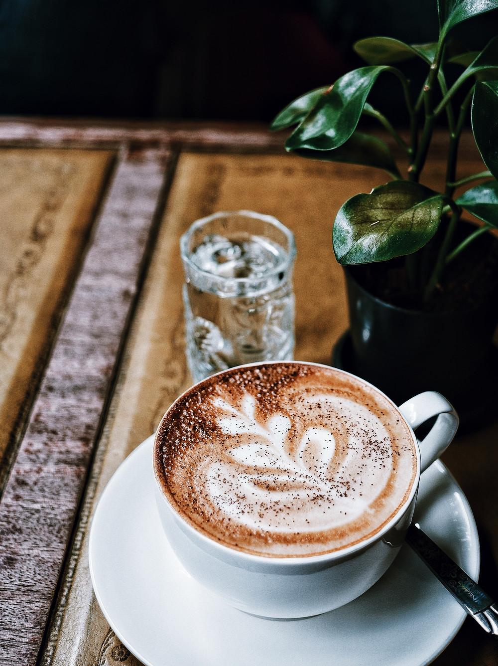 Café mocha dans une tasse blanche sur une table en bois à coté d'une plante