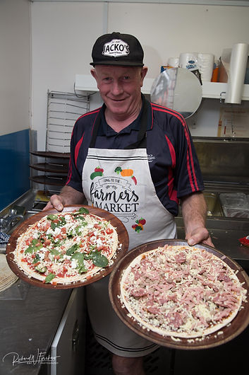 Jack serving pizza at the farmer's market