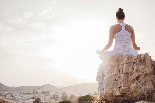 mulher-tranquila-meditando-ao-por-do-sol