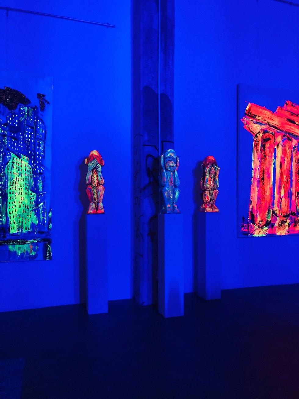 Statuen und Bilder mit fluoriszierender Farbe im Schwarzlicht
