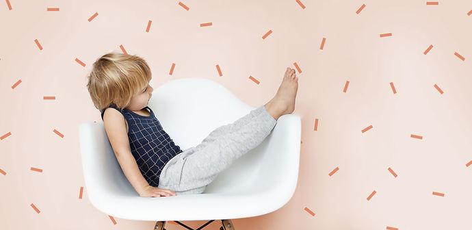 Junge sitzt auf weißem Stuhl mit rosa Hintergrund