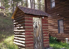 historic CCC built outhouse at Camp Custer Log Cabins