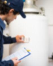 Plumber repairing an hot-water heater.jp