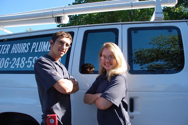 Plumbers in front of work truck