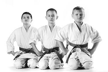 Karate boy in kimono fighting on a white