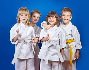 Four cheerful sportsman in karate gi are