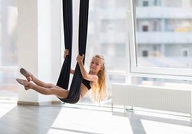 Adorable girl in hammock in aerial yoga