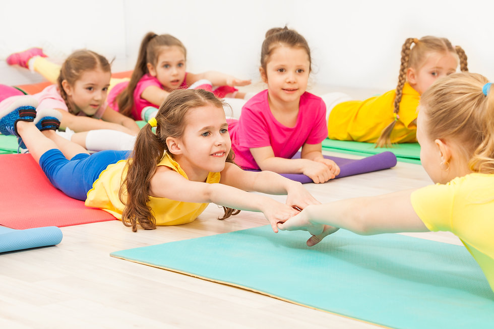 Kids practicing gymnastics with female t