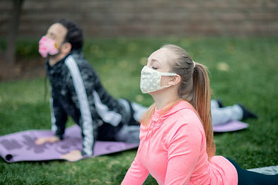 Young couple practicing yoga wearing clo