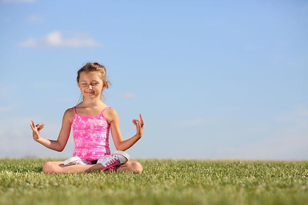 Happy little girl meditates on green fie
