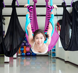 Woman making aerial yoga exercises, indo