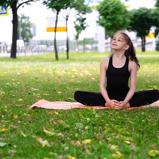 Gymnast schoolgirl warming up in a grass