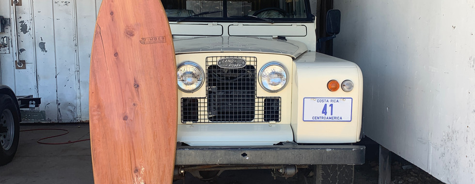 Timber Surf Company Wooden Surfboard in fron tof Jeep