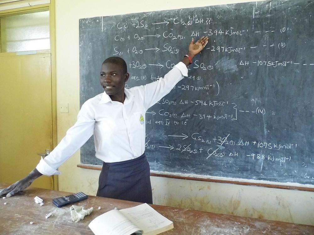 An Ugandan educator teaches a science lesson; image courtesy Pixabay.