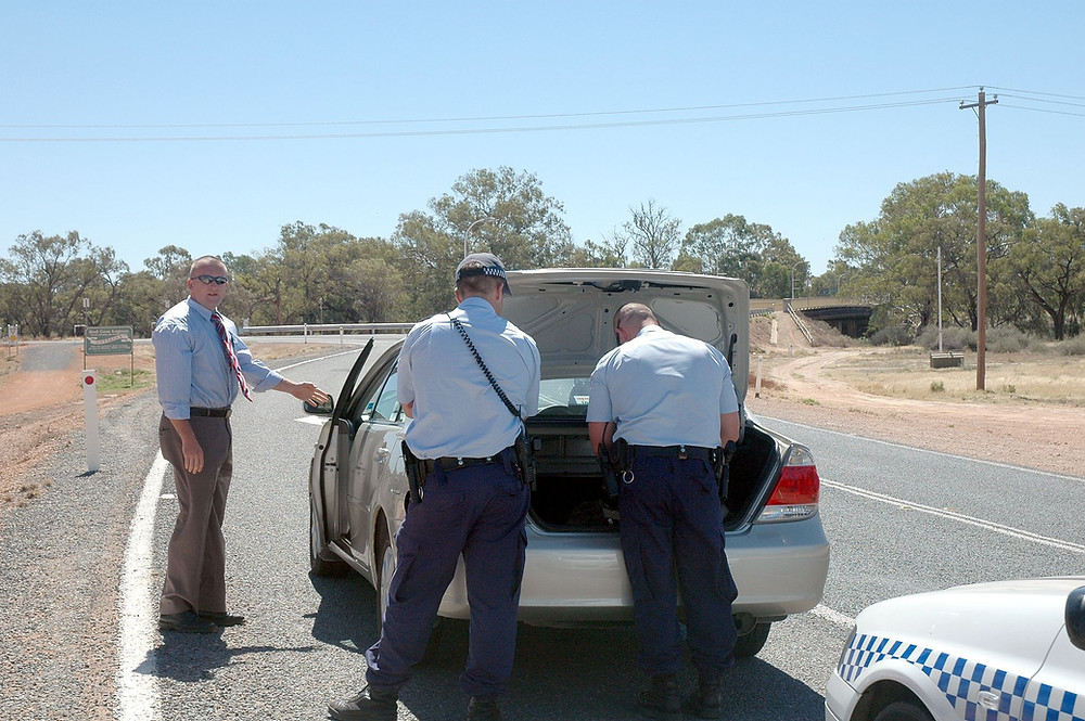 Police in Australia search a vehicle.
