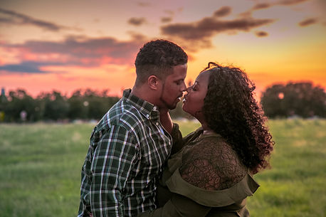 a couple kissing in front of a sunset