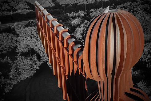An aerial view of the Angel of the North. A rust coloured metal structure of a human with large rectangular metal wings