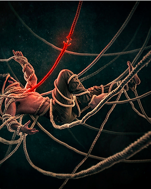 A man tangled in a series of ropes hanging from the ceiling