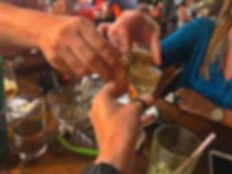 Grupo de amigos com copos de cachaça brindando.