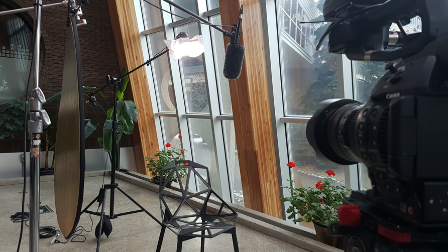 An interview setup of lights, camera, and microphone, with an empty chair in an atrium building