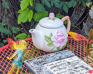 teapot with pink rose on red table besides prayer of serenity plaque