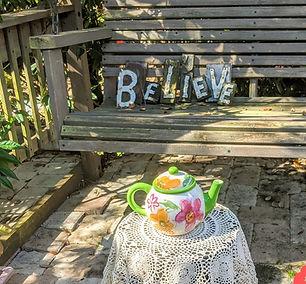 flowers design teapot in front of garden swing