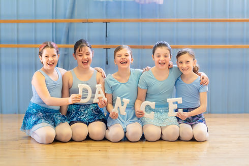 young ballerina's holding DANCE letters smiling and laughing