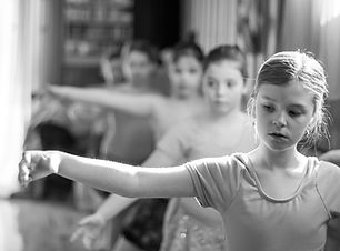 young ballerina concentrating at the barre