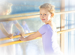 young ballerina at the barre smiling