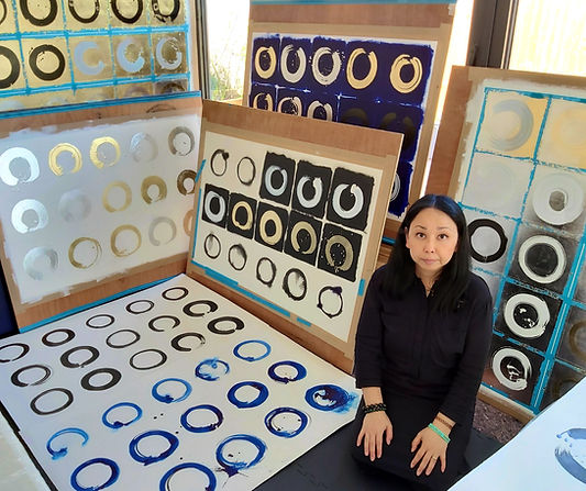 Artist Adele Cloony in her studio with 100 Days of Enso paintings