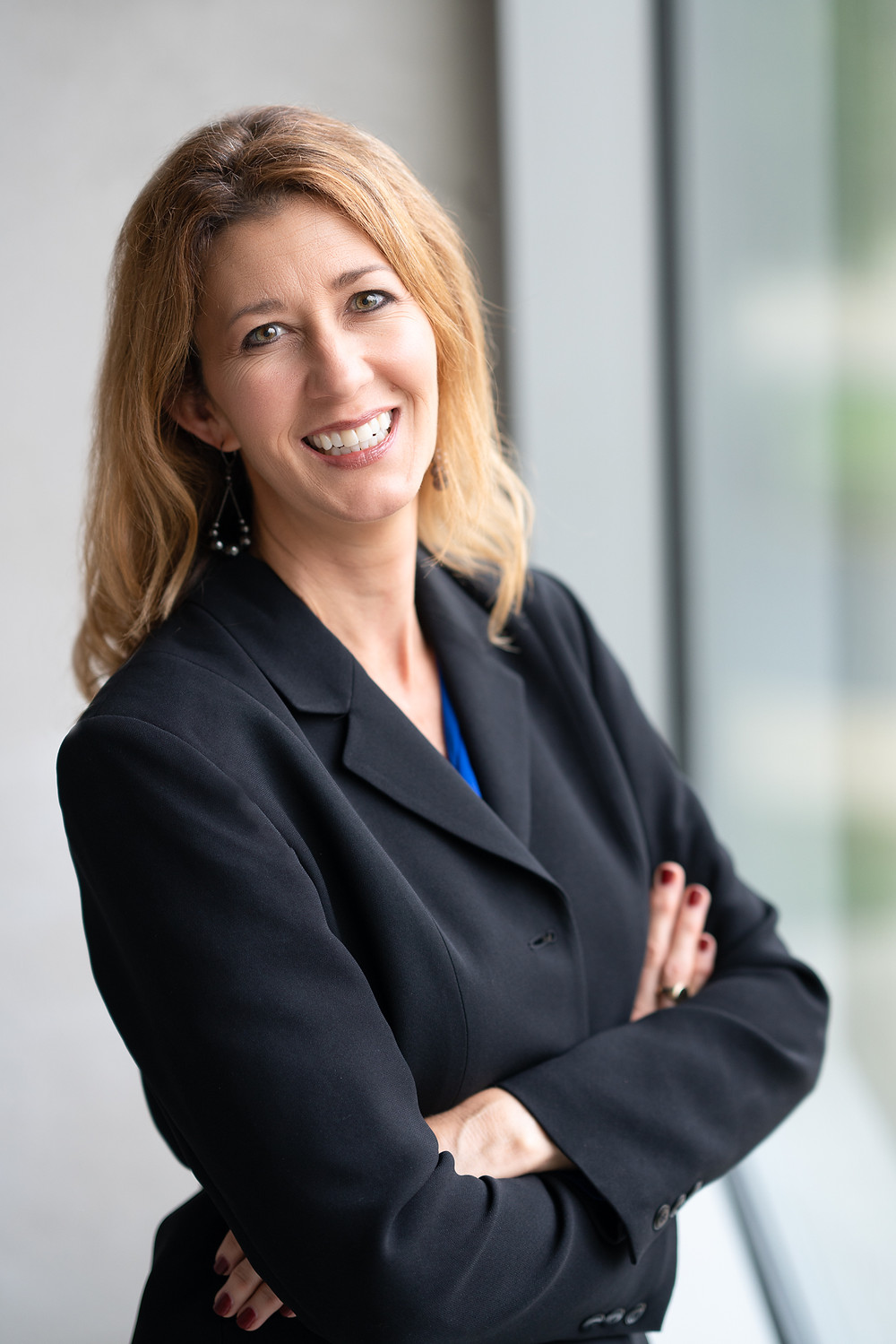 A woman wearing a business suit smiles for commercial headshot in Kalamazoo, Michigan