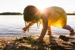 Girl Throws Sand at Sunset on Beach