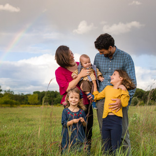 A Happy Family with Young Children Outdoors with a Rainbow in the Background