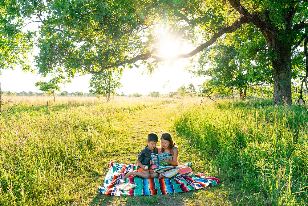 Two children are sitting on a blanket reading a book at a park in Kalamazoo, Michigan