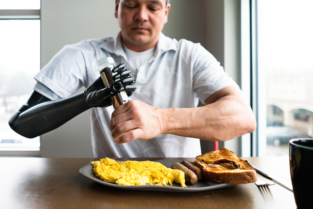 Man with a prosthetic arm using the pepper grinder at a restaurant