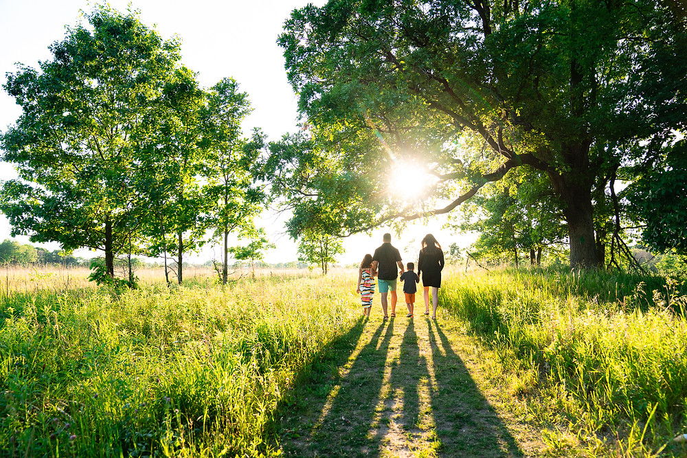 Family walking outdoors in Kalamazoo Michigan through forest at sunset