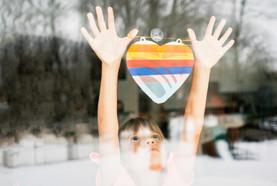 Girl hanging artwork on window