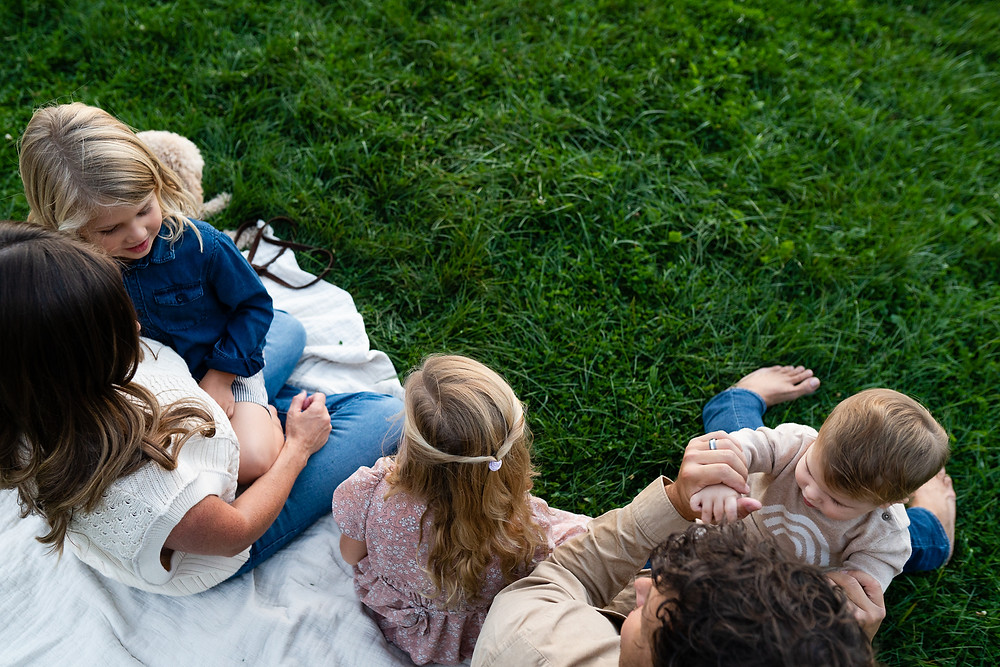 Overhead view of a family sitting together outdoors on a blanket