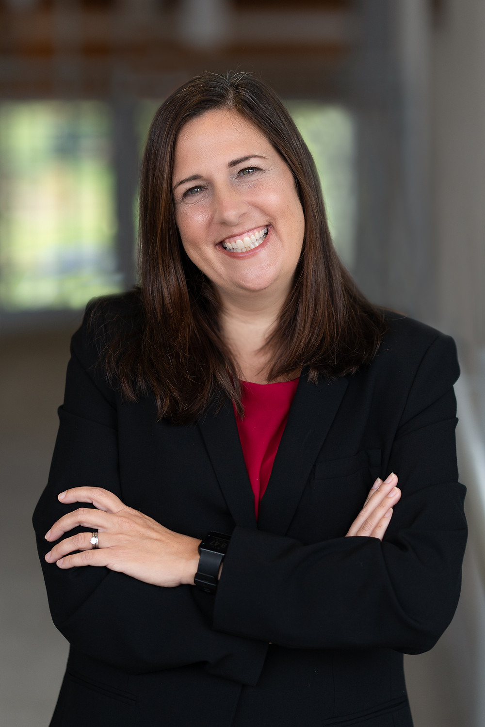 A middle aged woman wearing a suit smiles at camera for her commercial portrait