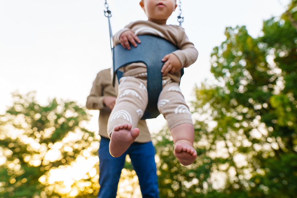 Closeup of a young babys feet who is sitting in a swing outdoors