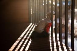Young Boy Looks Through Deck Rails
