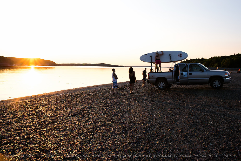 Group getting ready to paddleboard at sunset
