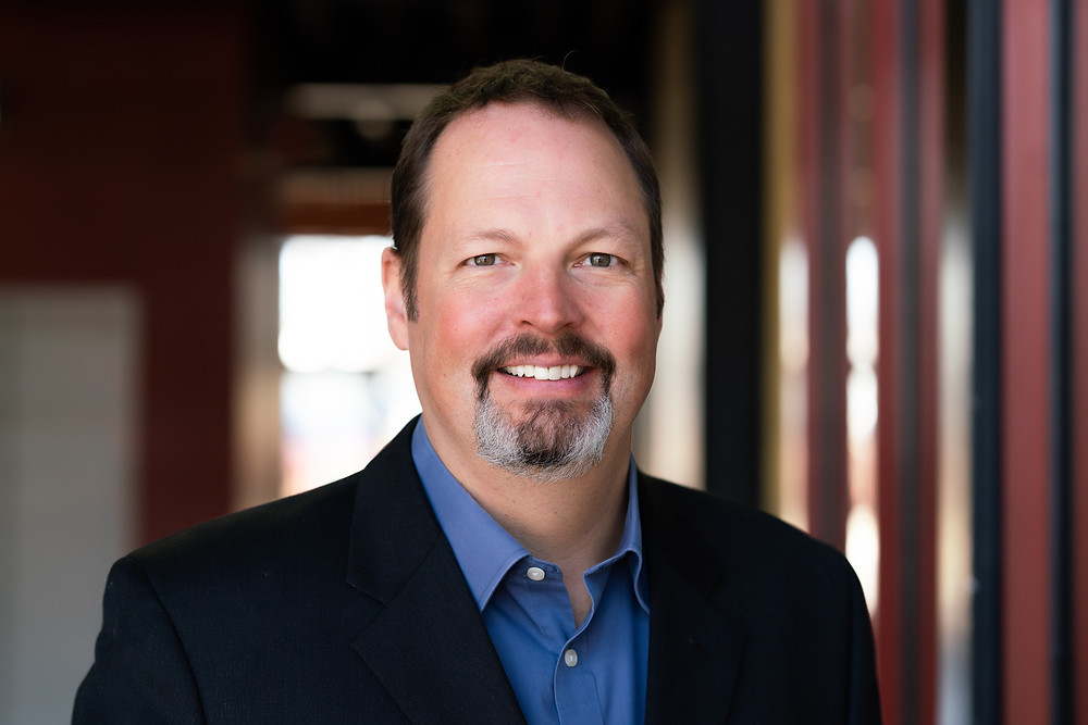 A man dressed in business casual smiling at the camera for his commercial portrait