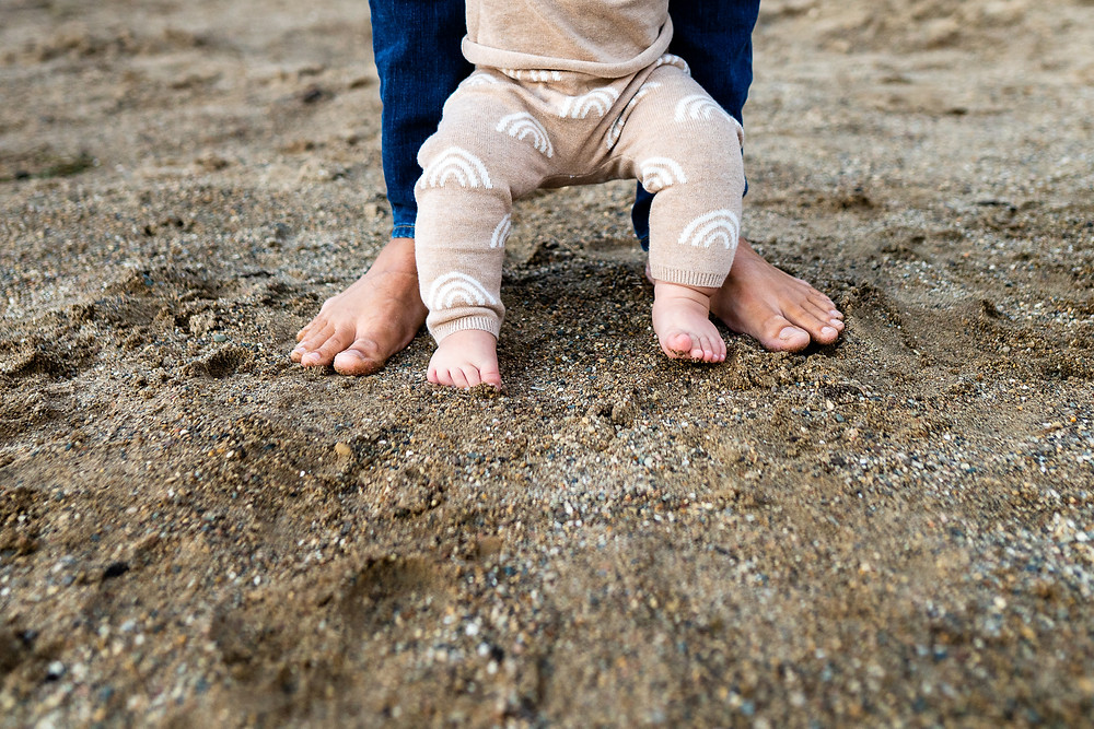 closeup of a babys feet with his fathers feet in the sand