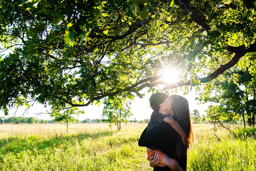 A mother and son hugging outdoors with sunlight coming through the trees in an outdoor park in Kalamazoo, Michigan