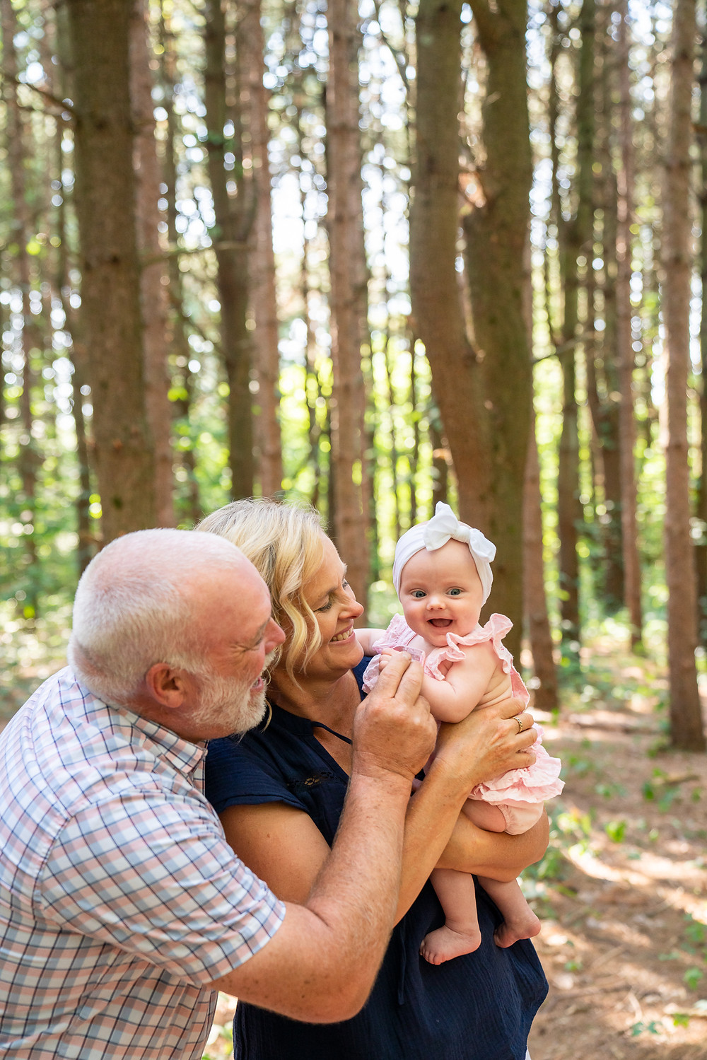 A grandma and grandpa holding a smiling baby outdoors