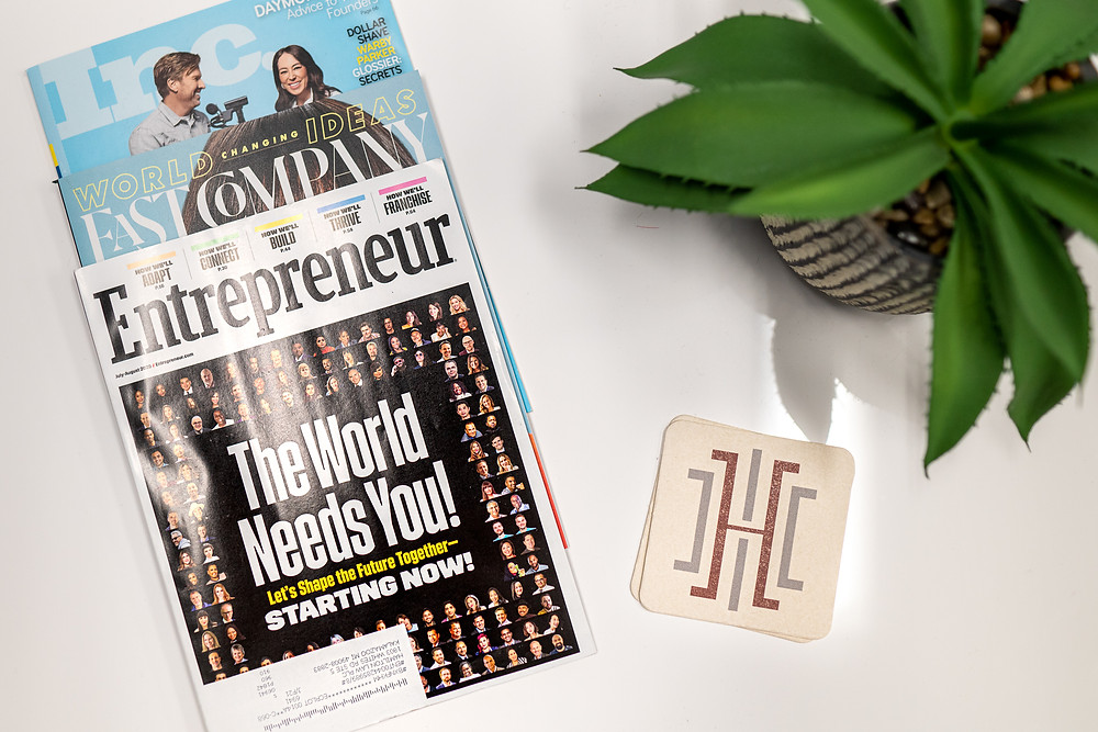 Overhead view of magazines and a plant on a table inside an office building