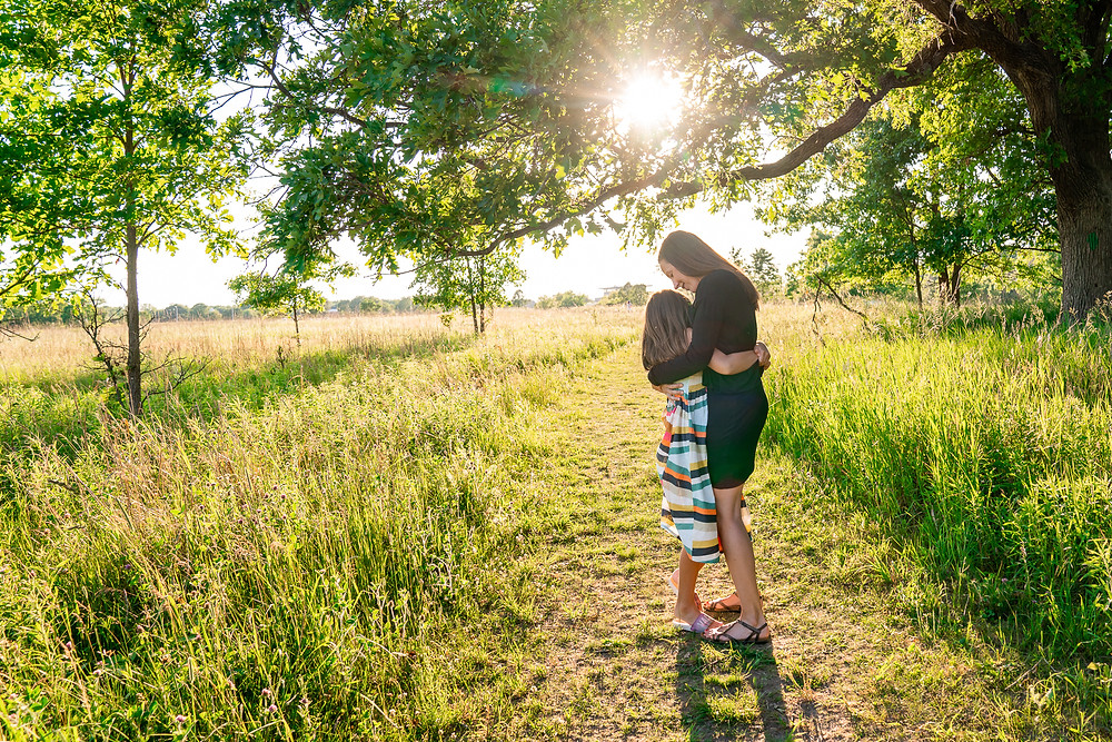 A mother hugging her daughter outdoors at a park in Kalamazoo, Michigan