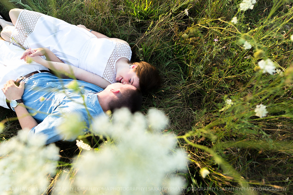 Couple laying together in a field at engagement session