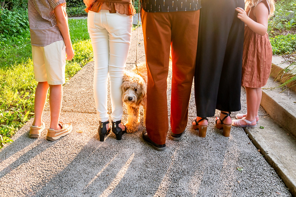 Family standing with their new puppy outdoors